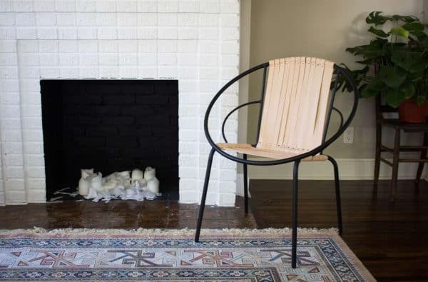 DIY leather chair with metal frame next to white fireplace