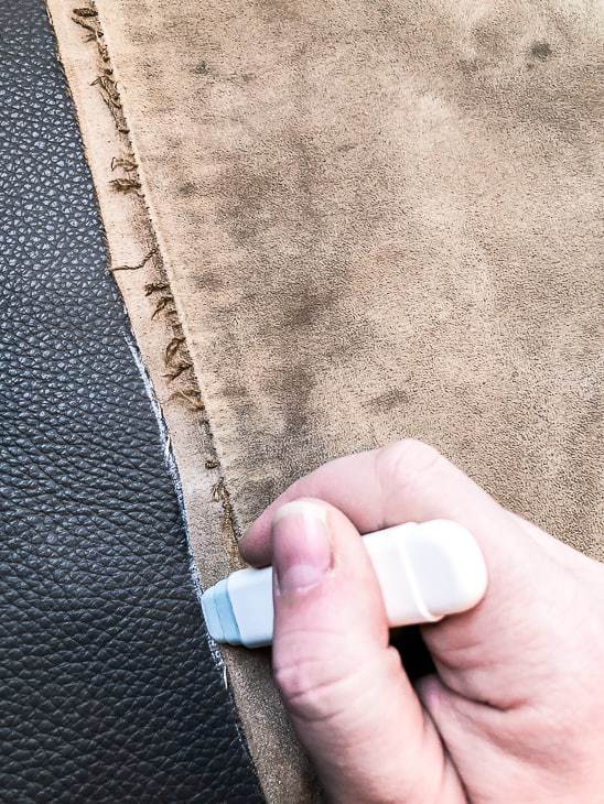 piece of fabric being traced with a chalk wheel on leather