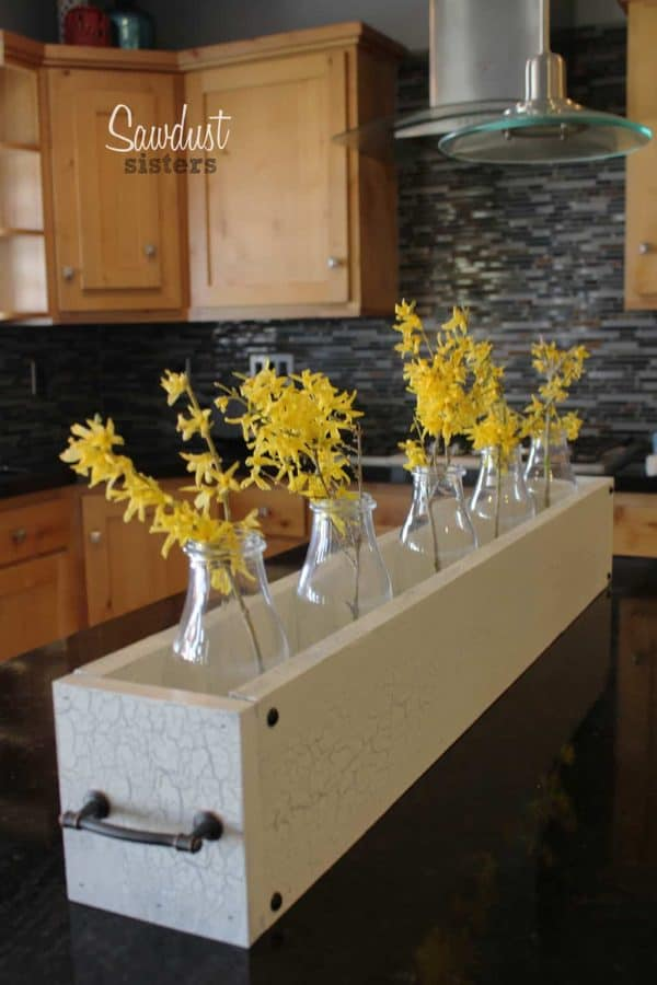 long wooden bin on a countertop holding jars with yellow flowers