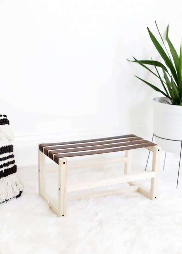 DIY leather footstool with white frame and brown leather on a white rug