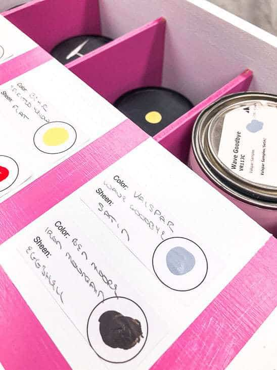 white box with pink box dividers holding paint samples, with labels on the lid