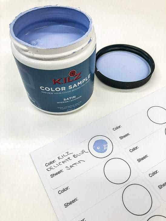 open jar of blue paint with sheet of labels indicating color and sheen