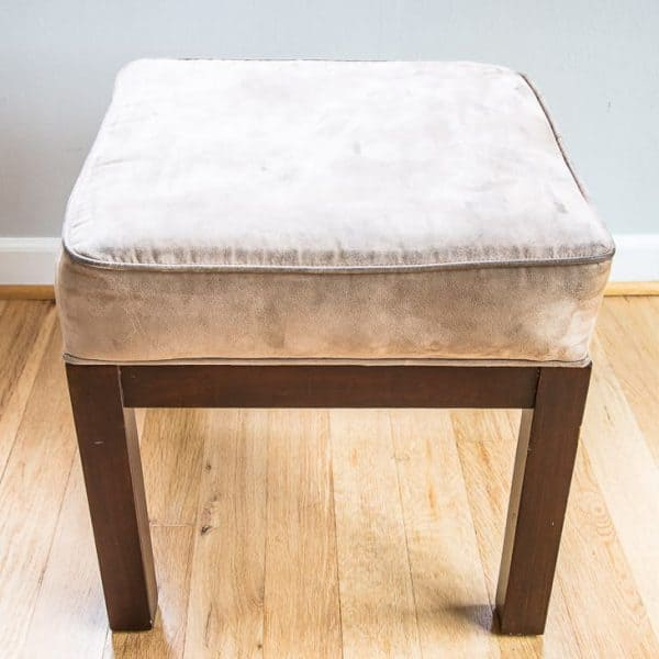 tan ottoman with dark brown wood base