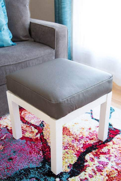 gray leather ottoman with white base next to gray couch