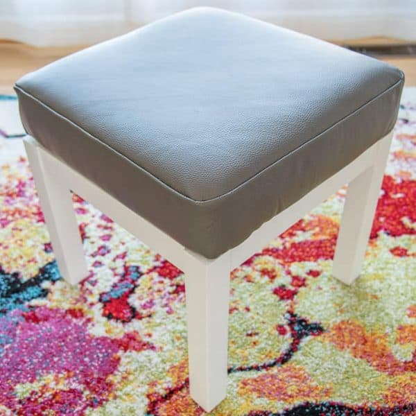 gray leather DIY ottoman cover with white base on colorful area rug