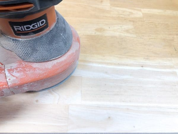 orbital sander removing old stain from tabletop