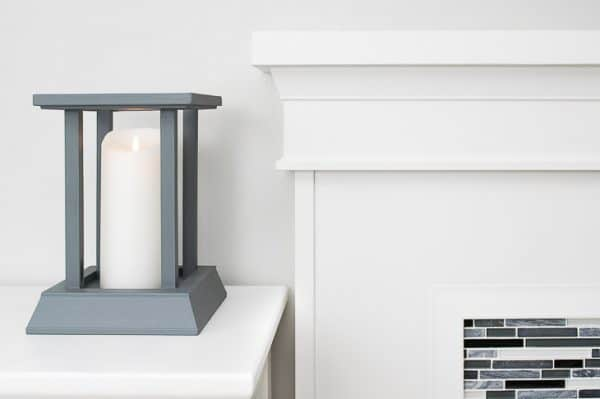 DIY candle lantern next to fireplace mantel