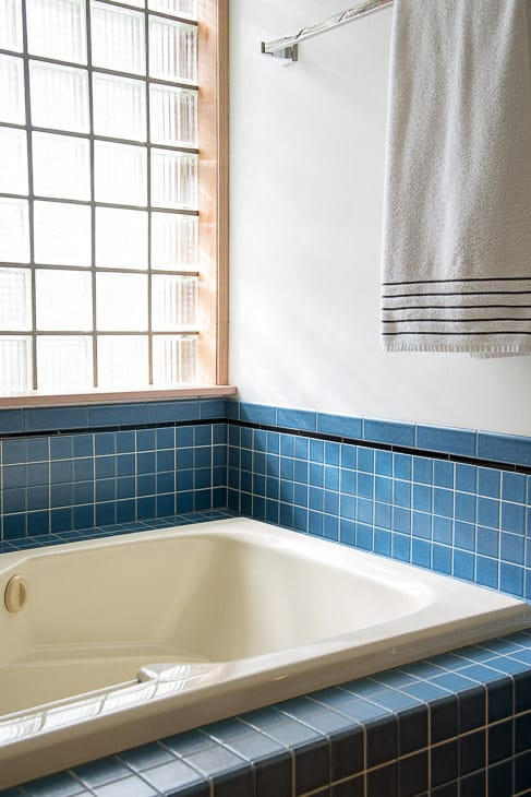 Almond bathtub with blue tile walls and glass block window