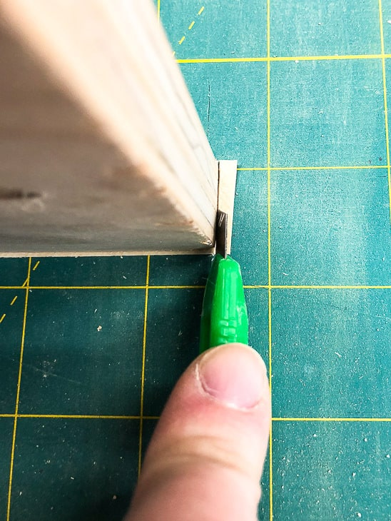 cut end of edge banding with razor blade on cutting mat