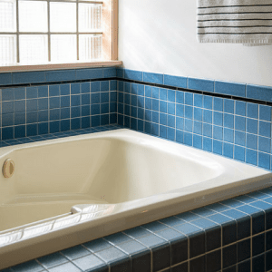 almond bathtub with glass block window and blue tile