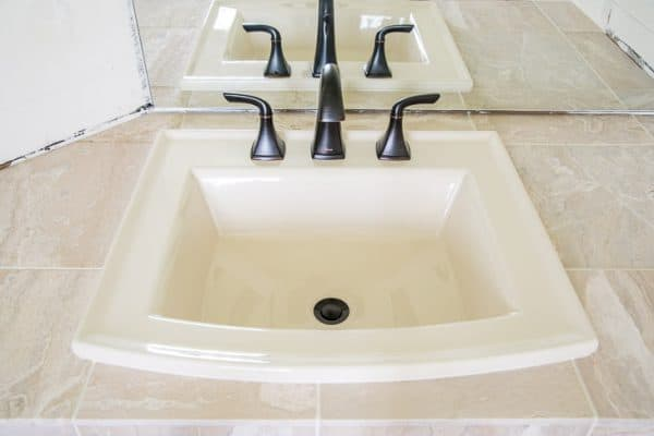 limestone tile vanity countertop with almond sink and oil rubbed bronze faucet