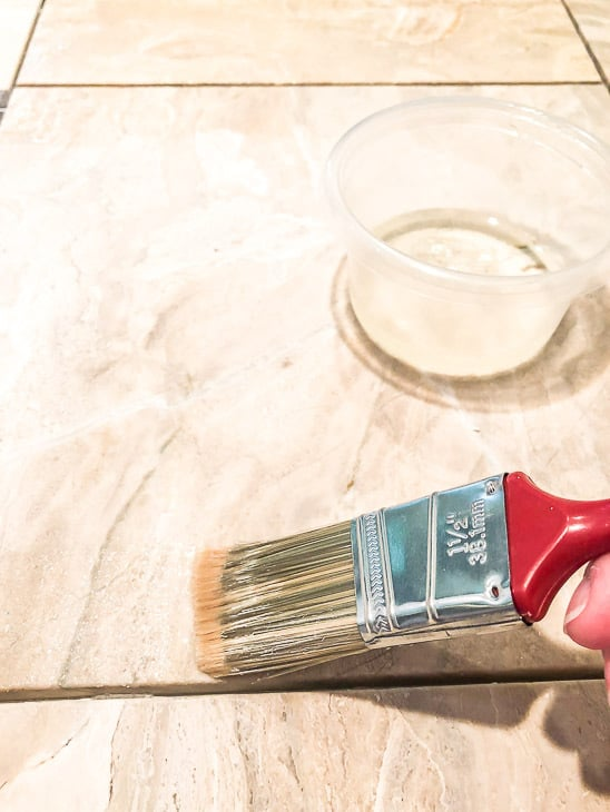 Applying grout release on limestone tile with a paint brush