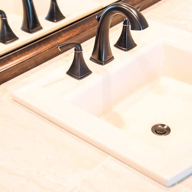 almond sink with limestone tile
