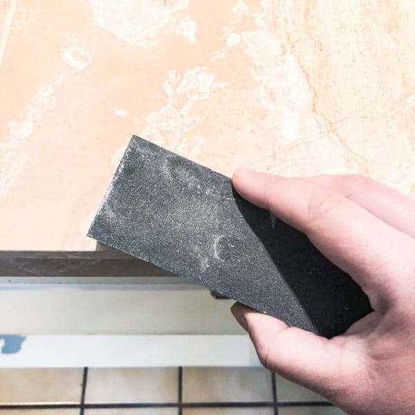 sanding stone on corner of limestone tile