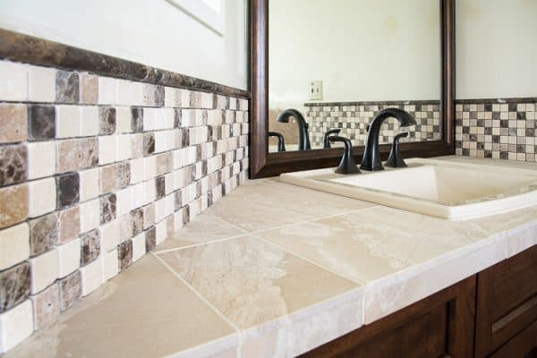 bathroom vanity with mosaic stone tile backsplash and limestone countertop