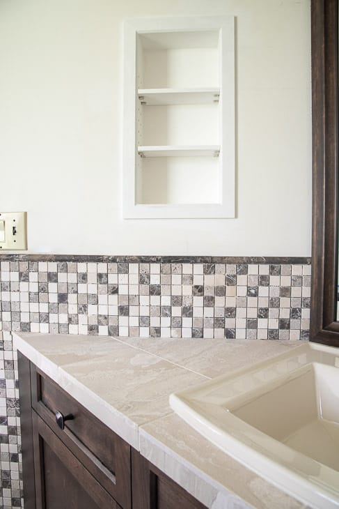 bathroom vanity with stone mosaic tile backsplash and recessed shelves above