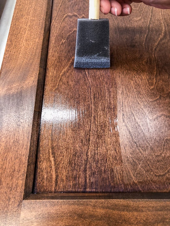 brushing on top coat on new cabinet doors
