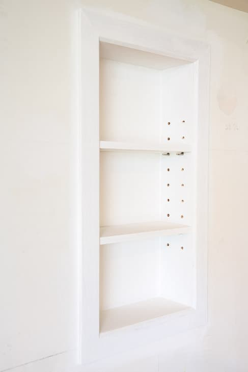 White recessed bathroom shelves with adjustable shelves