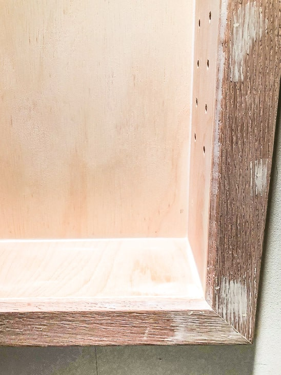 Filling gaps and holes in the recessed bathroom shelves with wood filler and caulk