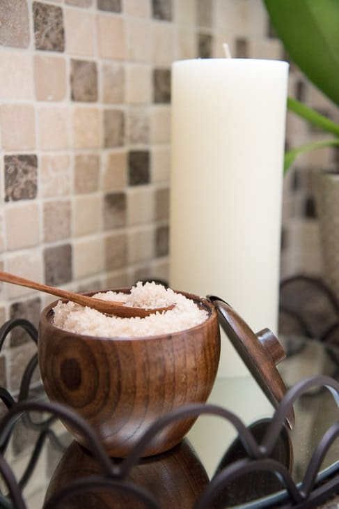 bath salts in wooden bowl with spoon and candle