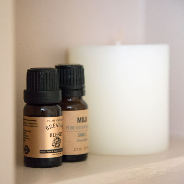 close up view of essential oils and candle in recessed shelves