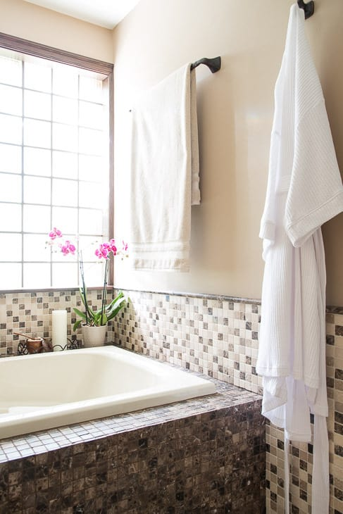 bathtub with mosaic tile walls, towel and robe hanging on wall