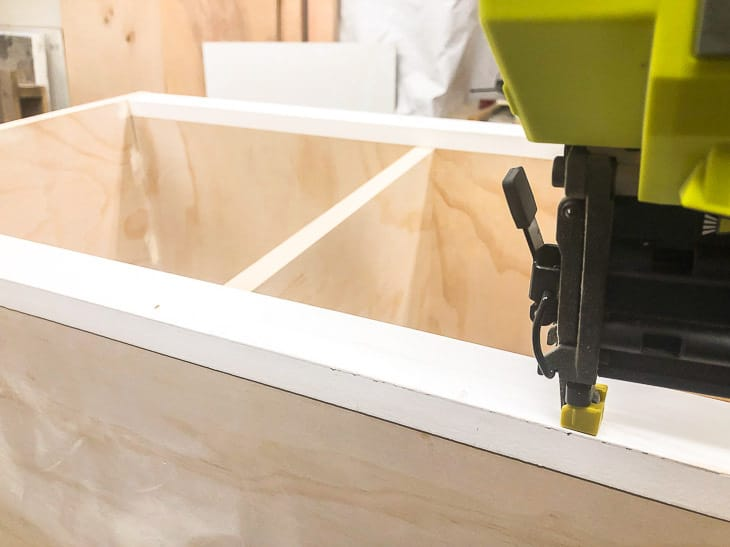 nailing trim boards to top and bottom of DIY entryway bench with nail gun