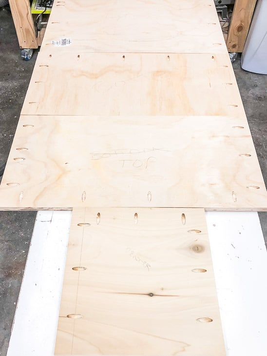 pocket holes drilled into plywood pieces for DIY entryway bench