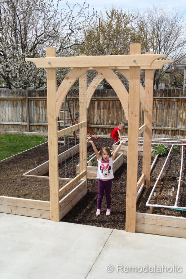 gothic arch arbor at entrance to raised planter bed garden