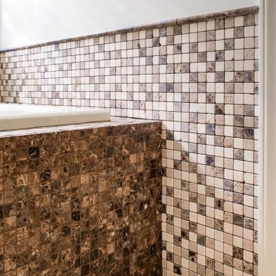 bathtub surround tiled in dark brown mosaic tiles with coordinating wall tile