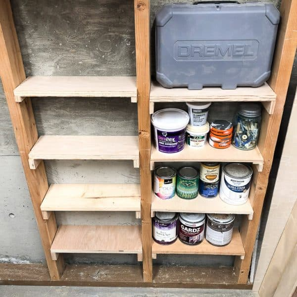 between the studs shelving half filled with paint cans