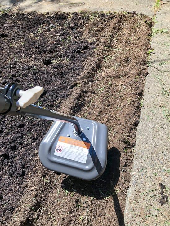Ryobi cultivator tilling soil in overgrown garden