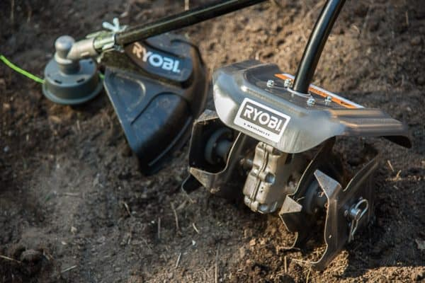 ryobi expand-it system cultivator and string trimmer attachments in empty garden bed
