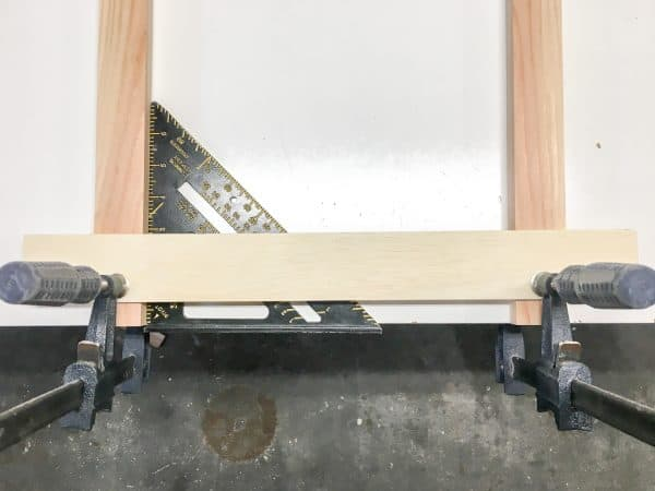 two upright boards clamped to one crosswise slat