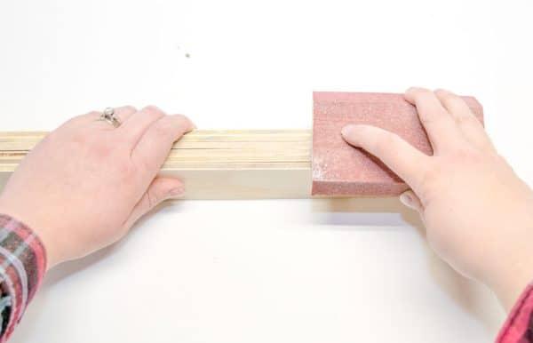 sanding edges of plywood slats for DIY martial arts belt display