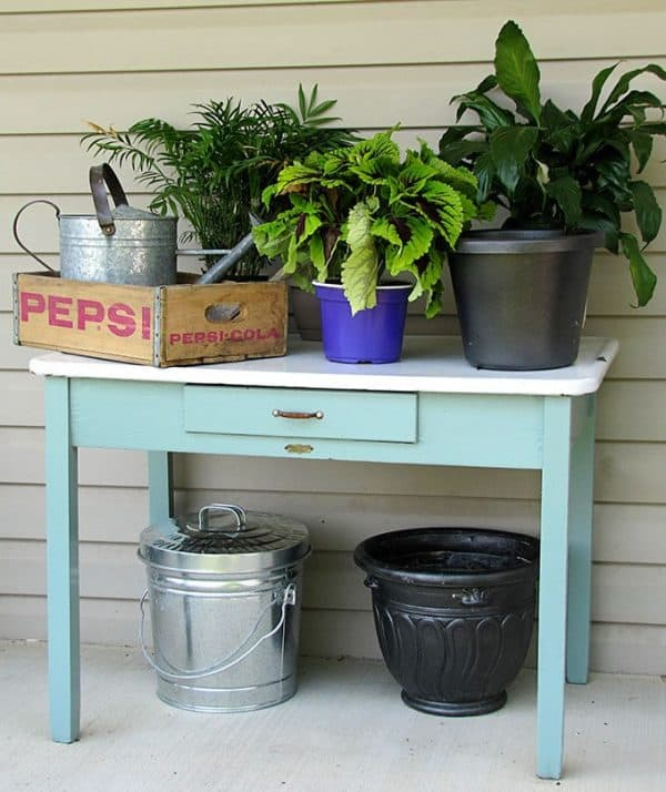 turquoise potting table with plants on top