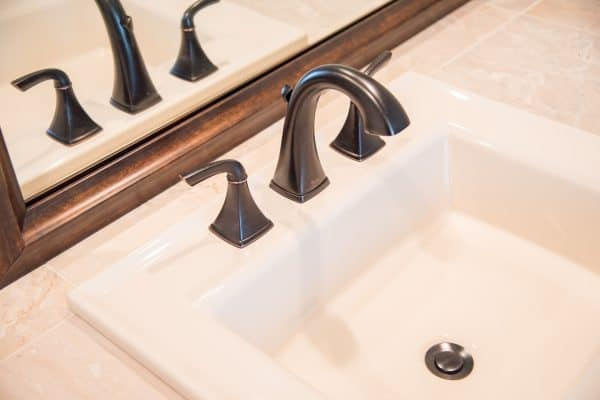 almond sink with oil rubbed bronze faucet and limestone tile countertop