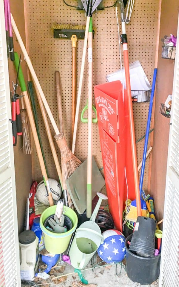 small gardening shed cluttered with tools and junk