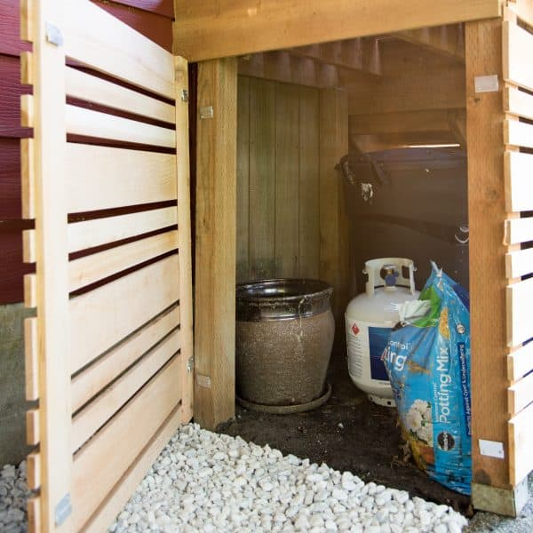 under deck stairs storage area with removable fence panel at end