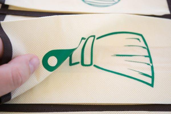iron on vinyl adhered firmly to fabric of garden tool organizer
