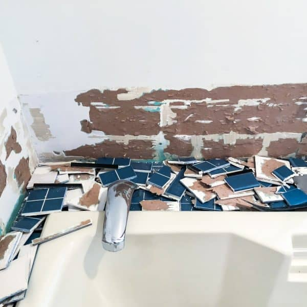 blue bathroom tile removed and torn drywall paper