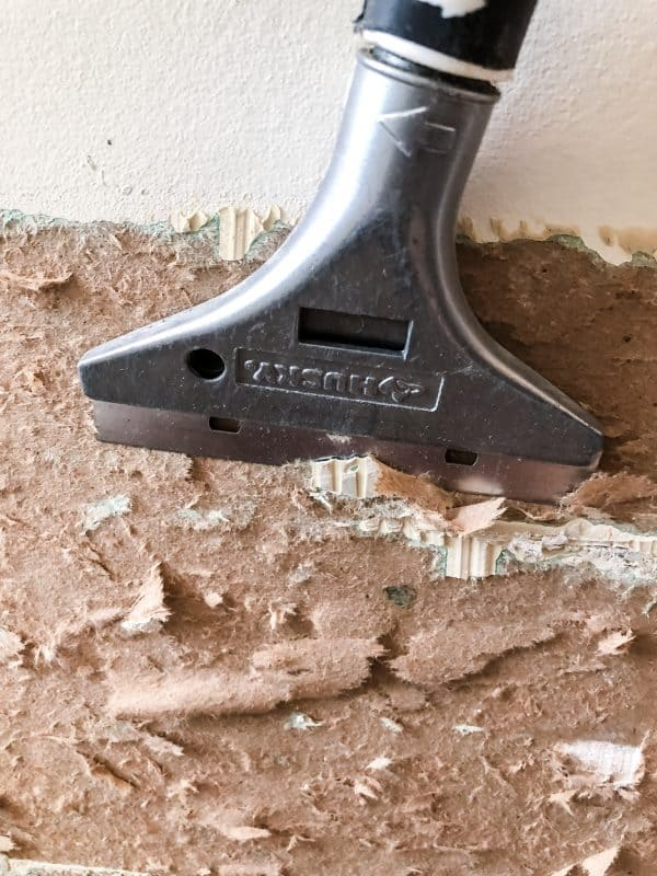 scraping away loose, torn drywall paper with a scraper tool