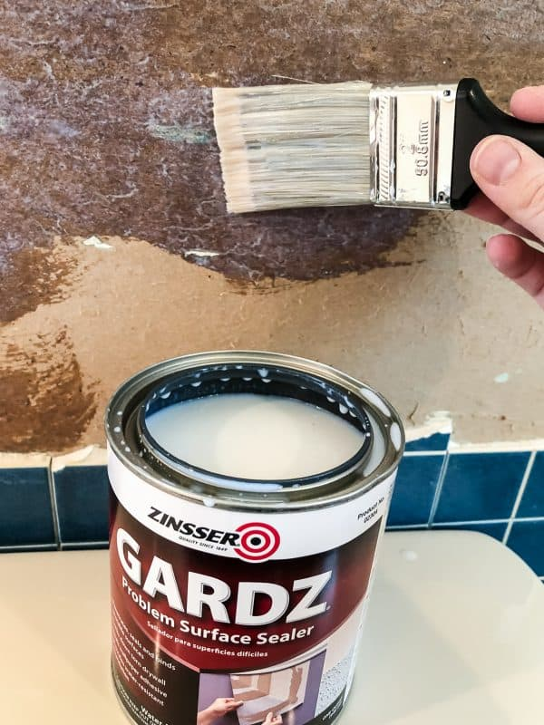 applying Zinsser Gardz to torn drywall paper with paint brush