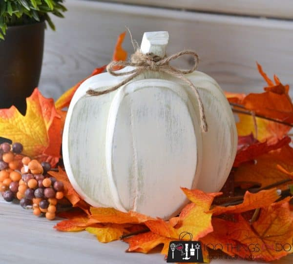 white wooden pumpkin surrounded by fall leaves