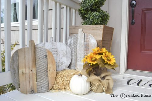 wooden pumpkins made from pallets on white porch