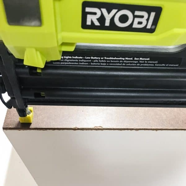 attaching the back of a cordless drill storage rack with a Ryobi Airstrike brad nailer