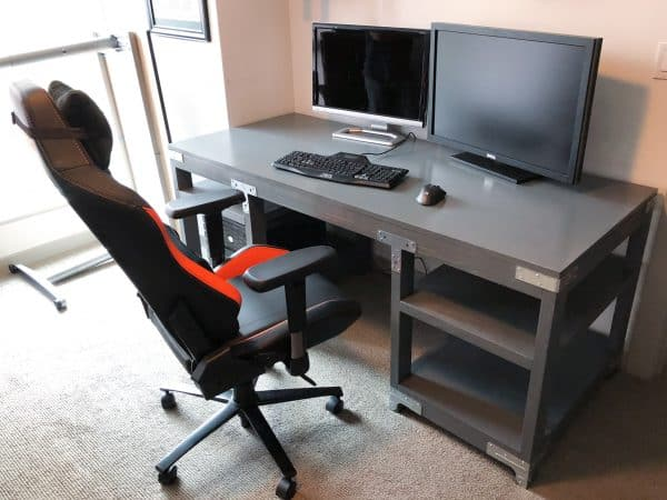 industrial desk with computer monitors and desk chair