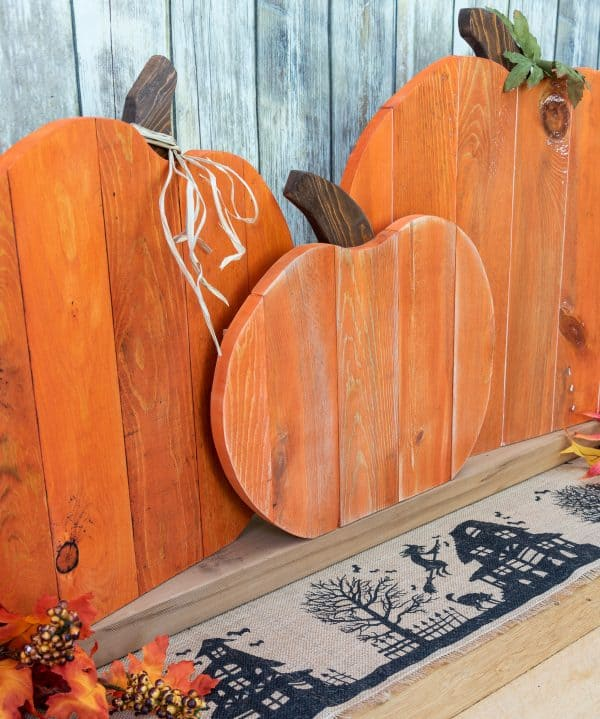three wooden pumpkins made from pallets on a burlap table runner with faux leaves
