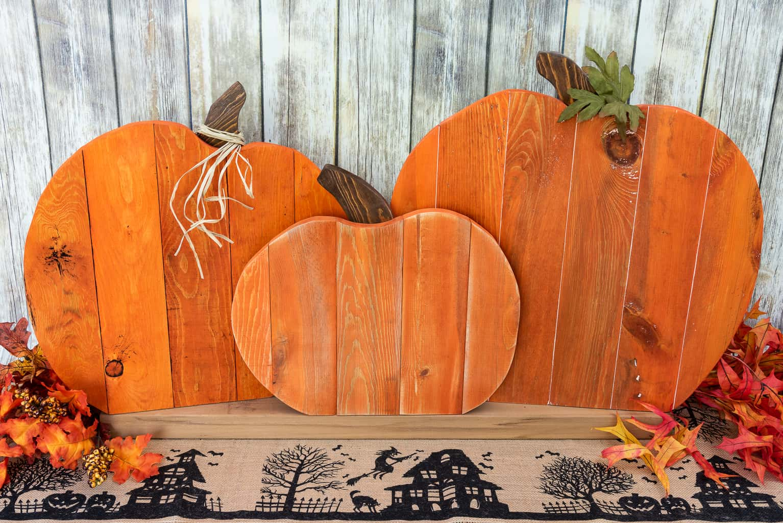 pumpkin pallet trio surrounded by fall leaves in front of a rustic background
