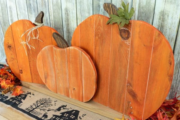 three pallet pumpkins in front of a rustic background
